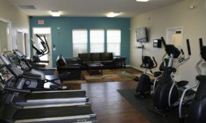 View of our fitness center with aerobic equipment like treadmills and ellipticals at our Lawrence apartments.