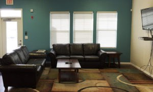 Fitness Room view with leather couch in common area at our Lawrence apartments.