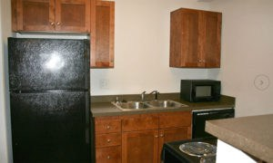 Kitchen with black appliances and cherry-wood cabinetry in our Lawrence apartments.