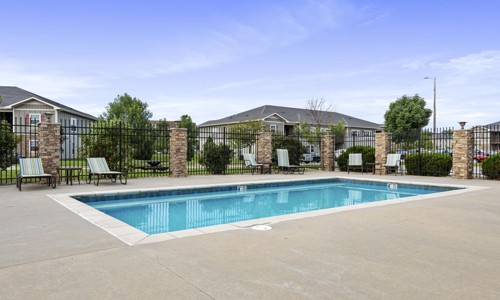 Sparkling in-ground pool with pool chairs at Remington Square in Lawrence